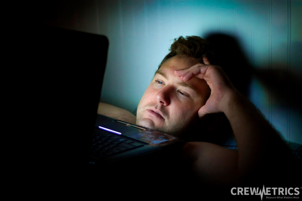 Tired man looking at laptop computer screen